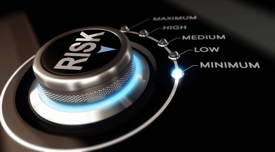 Switch button positioned on the word minimum, black background and blue light. Conceptual image for illustration of Risk management or assessment.